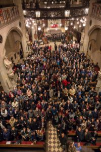 All the attendees gathered in the church. Picture taken from above the crowed with everyone looking up at the camera.