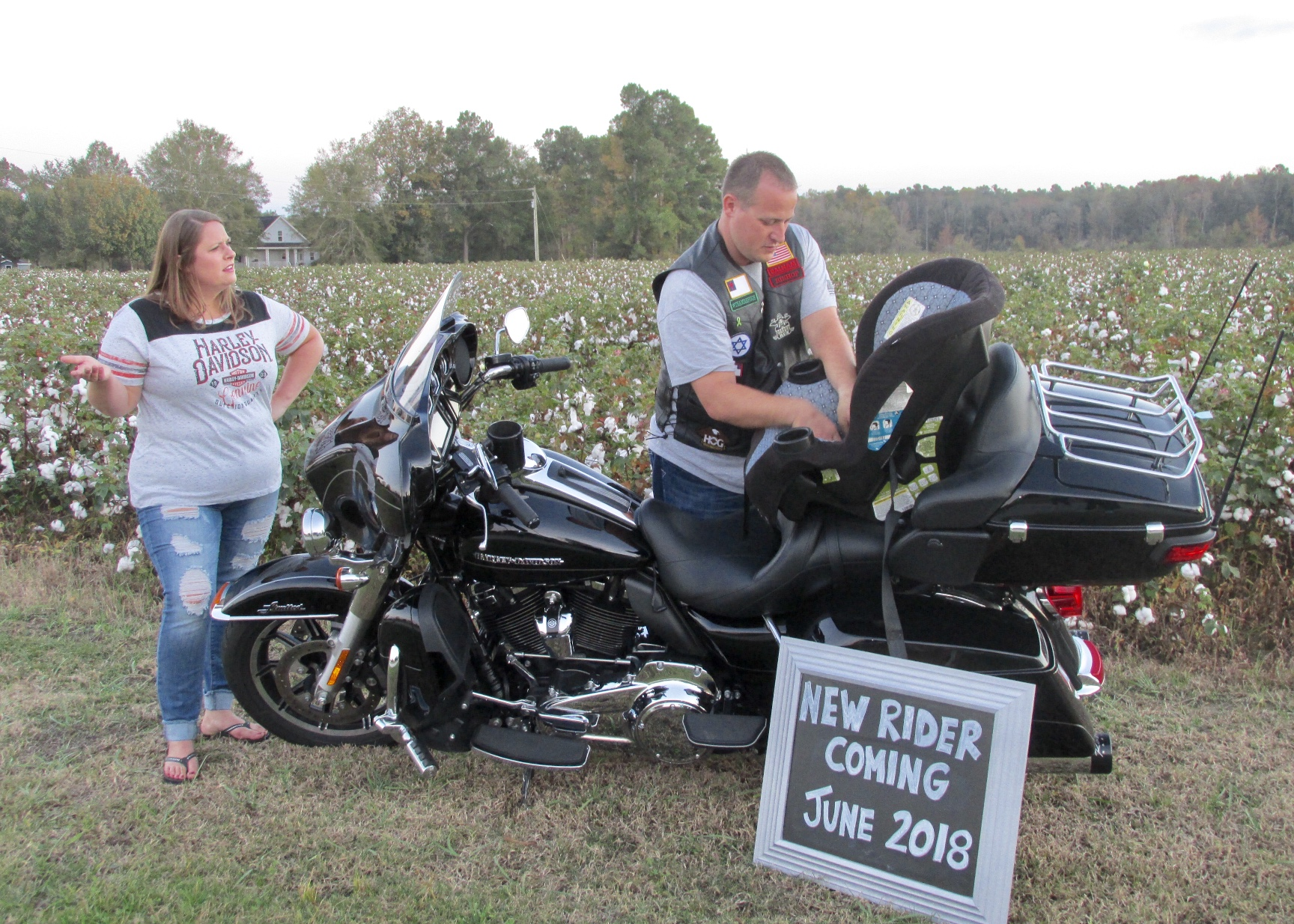 "Picture of the Cook's standing with a motorcycle and a sign reading ""New Rider Coming 2018."""