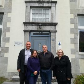 Mark and Jeannie McClung standing with Pastor Darius and his wife, Margot in front of a building