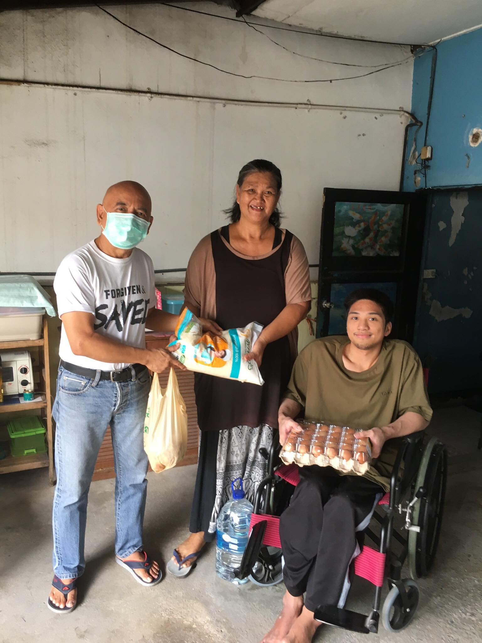 Albert is giving relief goods to a family member of Don Muang Church