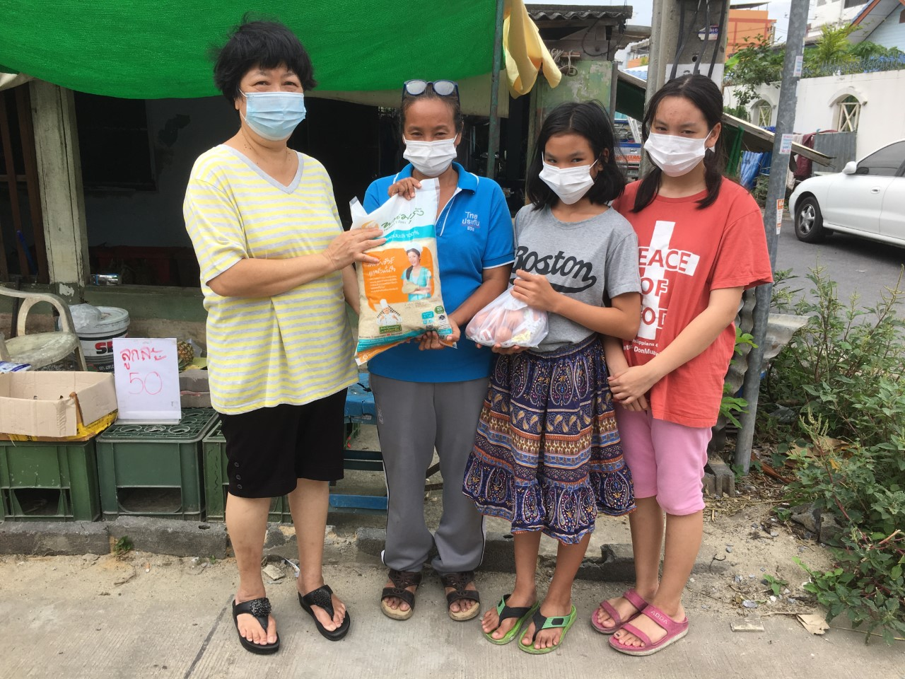 Jiep is giving relief goods to a family member of Don Muang Church
